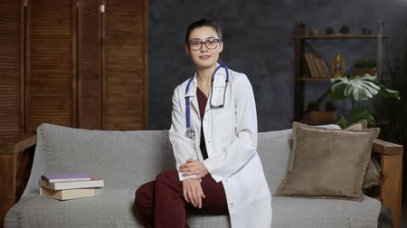 Professional woman doctor with stethoscope and glasses talking to camera sitting on the couch.