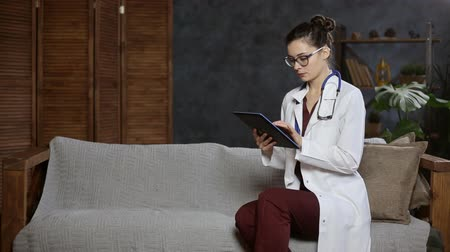 Portrait of a woman doctor with stethoscope using tablet computer on the couch, copy space
