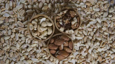 Assortment of different kinds of raw nuts in small wooden bowls - walnut, almonds, cashews and peanuts. Rotation video. Top view.