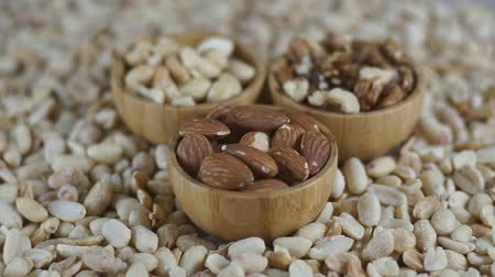 Set of various raw nuts in wooden bowls - walnut, almonds, cashews and peanuts. Rotation video. Стоковые видеозаписи