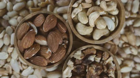 Top view of various raw nuts in wooden bowls - walnut, almonds, cashews and peanuts. Rotation video. Стоковые видеозаписи
