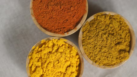 Top view of three various spices in wooden bowls on white desk - turmeric, curry, paprika. Rotation video. Стоковые видеозаписи