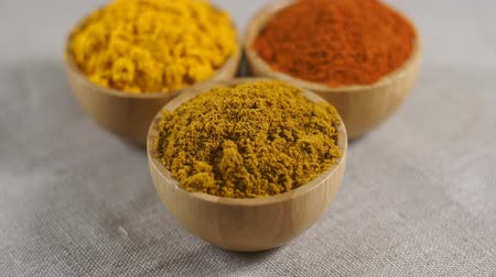 Set of various spices in wooden bowls - paprika, turmeric, curry. Rotation video.