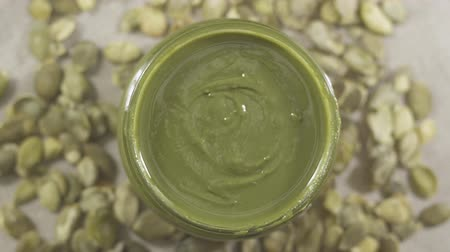 Top view of natural paste from pumpkin seeds in glass jar. pumpkin seed butter, urbech. Rotation video Dostupné videozáznamy