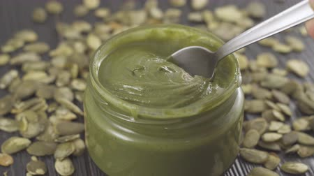 Pumpkin seed butter. Creamy paste from pumpkin seeds in jar on a table. Spoon on Natural nutrition and organic food.