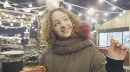 Portrait of happy smiling girl holding sparklers, posing at Christmas fair in European city.