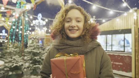 bengália : Portrait of young happy smiling girl posing with gift box at Christmas fair.