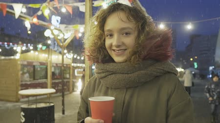 Portrait of young happy curly hair girl posing with cup of coffee at Christmas fair.