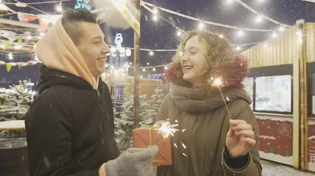 Excited young couple is celebrating new year with bengal lights or sparklers at Christmas fair Стоковые видеозаписи
