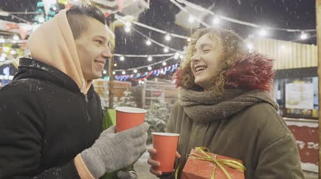 Excited young couple celebrating new year holding gifts and smiling at Christmas fair