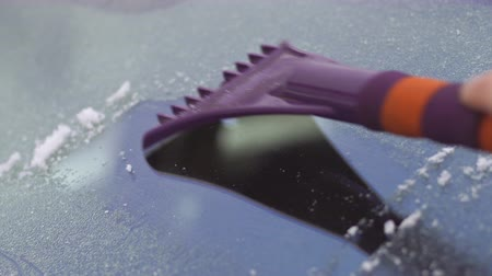 scrape : Driver cleaning the car window with a ice scraper, close up