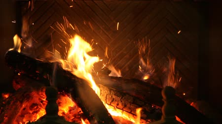 Round logs burn in a fireplace. Ancient brass fire iron corrects burning coals. Man hand puts next log into fire. HD video