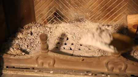 We clean fireplace from ashes with brass shovel. Cleaning the fireplace. Close up
