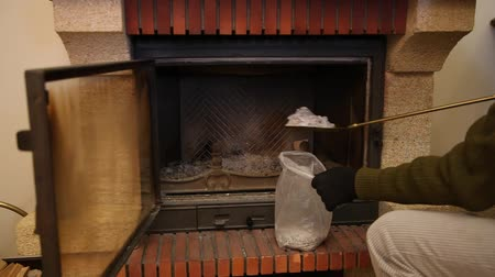 We clean fireplace from ashes with brass shovel. Cleaning the fireplace. Gloved hands collects it in a bag
