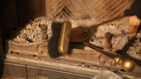 Hand cleans fireplace with brass brush and spatula. Cleaning the fireplace. Close up of a yellow blade close up