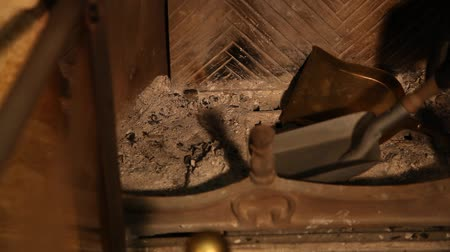 after fire : Hand cleans fireplace with metal spatula. Cleaning the fireplace. It is a gloss spatula.