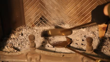firebox : Hand cleans fireplace with brass brush and spatula Cleaning the fireplace. The hand collects the ashes in the firebox with a brass brush on a long handle in the yellow blade close-up Stock Footage