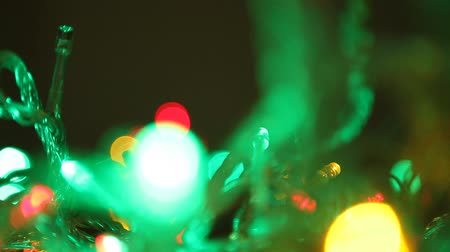 lüktet : Green lights of New Year garland blink close up. Bright green lights of a New Years garland actively pulsate in a dark room. Then they freeze and gradually slowly fade. Defocused image