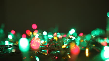 ритмичный : Flashing lights of New Year garland close-up. Bright yellow and green lights of a New Years garland actively pulsate in a dark room. Defocused image Стоковые видеозаписи