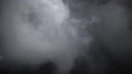 Slow-motion Dry Ice Smoke Clouds Fog Overlay. VFX atmosphere insert element. Haze background. Abstract smoke cloud. Smoke in slow motion on black background.