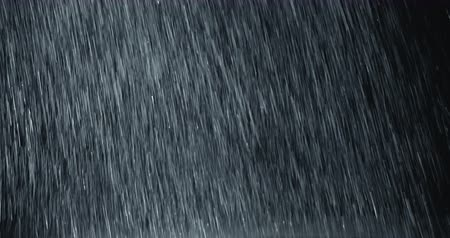 Vertical heavy rain falling in front of the camera against black screen. Raindrops splashing. Rain closeup vfx insert. Practical seamlessly loopable footage. Heavy rainstorm hitting black surface. Стоковые видеозаписи