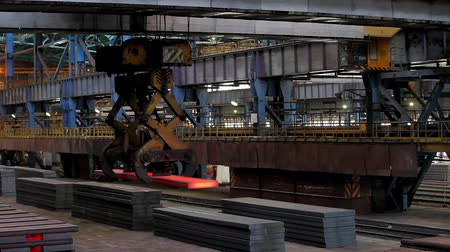 industry : Piles of hot steel ingots in warehouse moved with an ingot tong crane. Foundry casting process, black metallurgy manufacture. Stock Footage