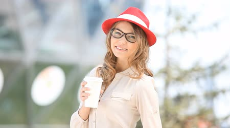 Happy young female student holding a coffee-to-go cup and smiling softly against urban city background.