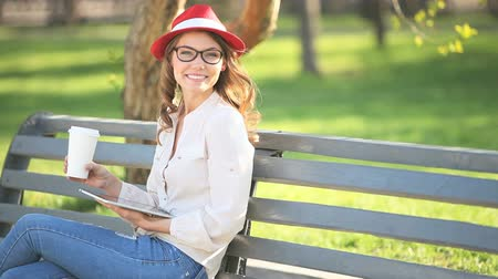 A happy young student with a tablet pc and a disposable coffee cup sitting on the bench in a summer park.