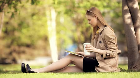 A smiling young woman with a tablet pc and a coffee cup sitting on the green grass in a summer park. Wideo