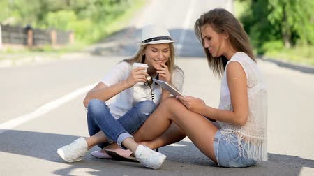 paylaşımı : Happy young women with vintage music headphones and a take away coffee cup, surfing internet on tablet pc together and having fun against urban city background. Stok Video