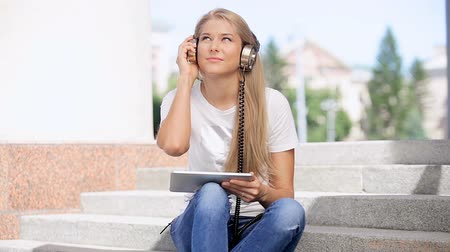 Happy young woman listening to the music in vintage music headphones, surfing internet on a tablet pc and sitting on stairs against urban city background.