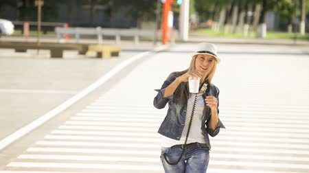 Beautiful young woman in a hat and jeans jacket with a disposable coffee cup, dancing, doing moonwalk on the road, drinking coffee, and smiling against nature background.