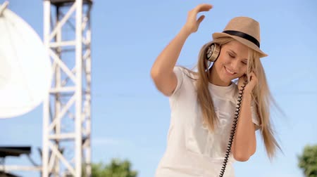 Happy young woman in hat wearing vintage music headphones, drinking takeaway coffee and posing against background of parabolic satellite dish that receives wireless signals from satellites.