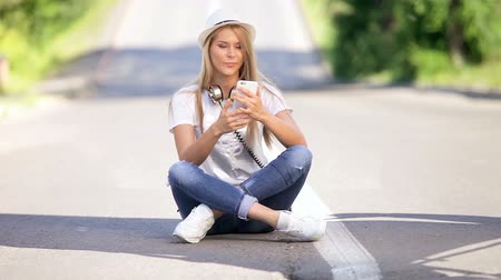 Happy young woman with vintage music headphones around her neck, surfing internet on a smartphone and sitting on a separating strip against road background. Wideo
