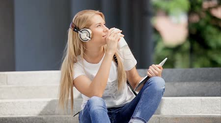 Happy young woman with vintage music headphones and a take away coffee cup, surfing internet on tablet pc, listening to the music and sitting on stairs against urban city background. Wideo