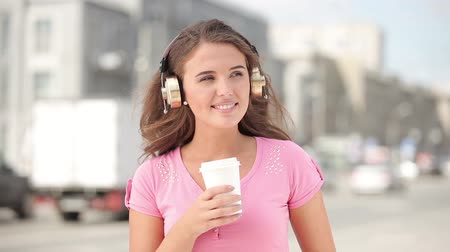 Happy young woman with music headphones, holding a take away coffee cup and bobbing her head to the beat of the music against city traffic background. Wideo