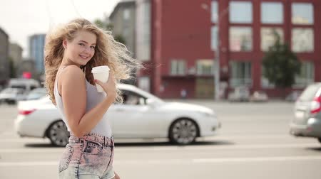 Happy young woman with long curly hair, holding a take away coffee cup, posing and flirting in front of a camera against city traffic background.