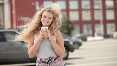 Happy young woman with long curly hair, holding a take away coffee cup and smiling with flirt in front of a camera against city traffic background. Wideo
