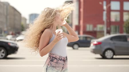 kıvırcık saçlar : Happy young woman with long curly hair, holding a take away coffee cup, posing and flirting in front of a camera against city traffic background.