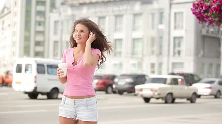 Happy young woman with music headphones, holding a take away coffee cup, bobbing her head to the beat of the music and going round and round against city traffic background.