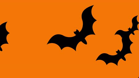Group of bats flying from one side to another on orange background.  Halloween themed background.