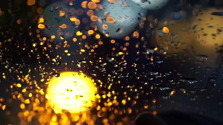 rainy : abstract blur blinking traffic lighting in the rain with bokeh