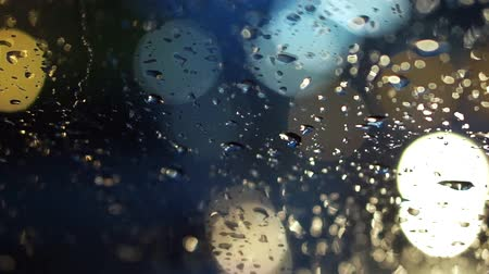 rainy : abstract blur traffic lighting in the rain with bokeh