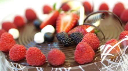 fırınlama : Hand cutting on pieces the Sticky chocolate cake with fresh strawberries and berrie Stok Video
