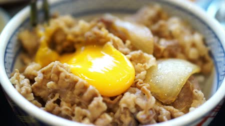 comida japonesa : Delicious eating raw egg yolk on food. Japanese beef over rice. Poached runny egg running out
