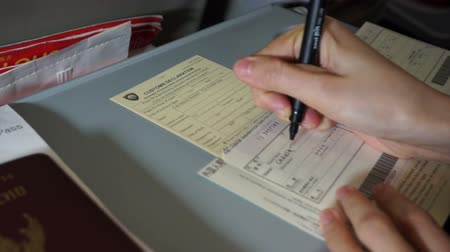 иммиграция : Tourist hand filling custom immigration form. Writing form on plane before landing