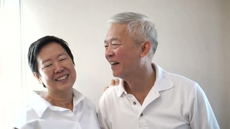 азиатский : Happy Asian senior couple on white background. Laughing and talking Стоковые видеозаписи