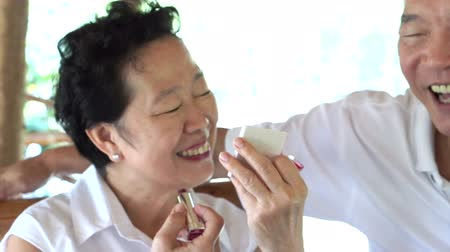 lasting : Happy lovely Asian senior couple, woman do make up lipstick and show to her husband. Long lasting love Stock Footage