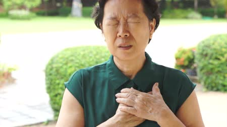 choroba : Senior Asian woman having heart attack, chest pain