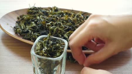 comida japonesa : hand setting dried green tea leaves